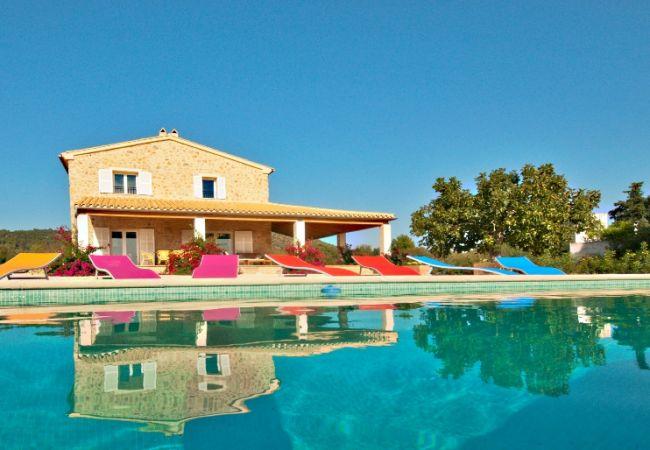 Fachada, piscina y tumbonas de colores
