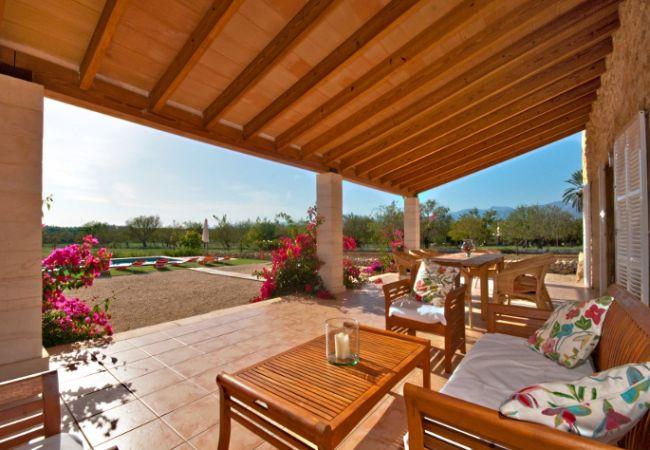 Terraza con sofás, mesa y vistas a la piscina