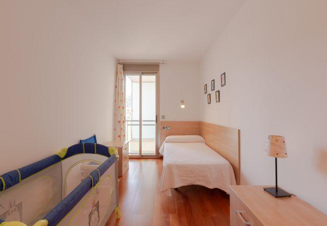 Dormitorio individual con una cama y cuna para bebé