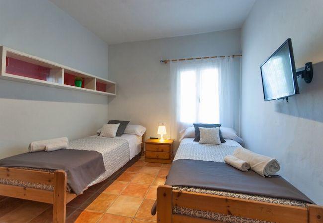 Dormitorio doble con dos camas individuales y televisión