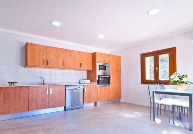 Cocina con lavavajillas, horno, microondas y mesa para comer