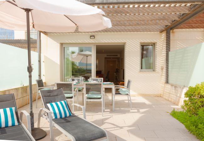 Terraza del apartamento con sombrilla y acceso a la piscina