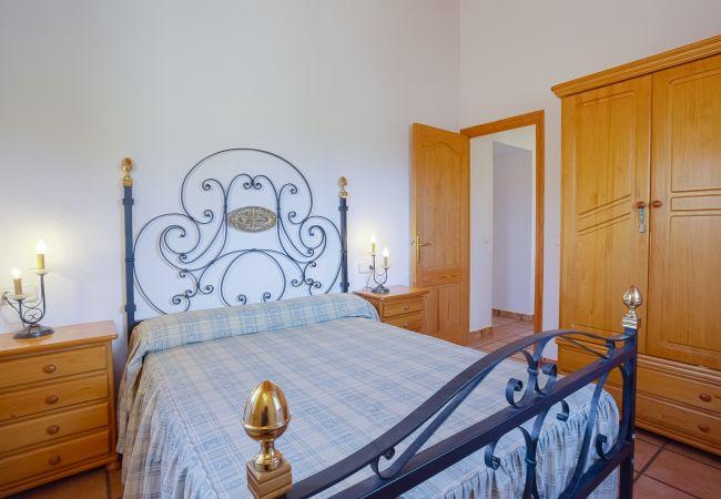 Cama doble en dormitorio con armario y mesitas