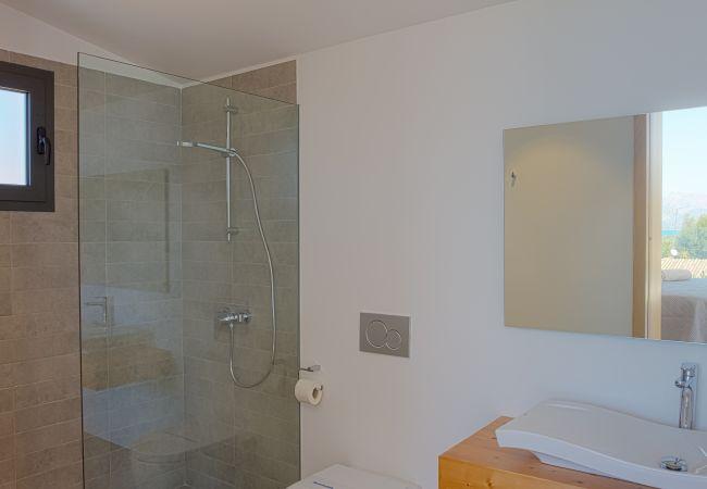 Badezimmer mit Duschwanne und Glasscheibe