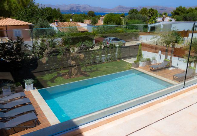 Blick von der Terrasse im ersten Stock auf den Pool und Garten