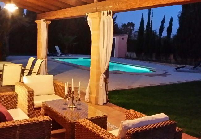 Porch mit Gartenmöbeln und Pool in der Nacht