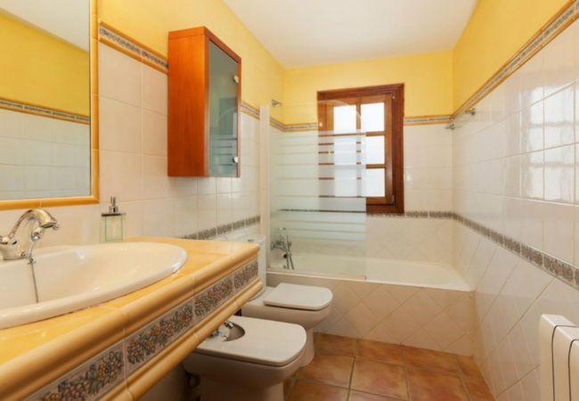 Badezimmer mit Badewanne, Glasscheibe, WC und Bidet