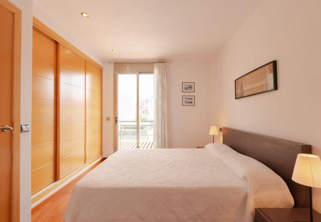 Schlafzimmer mit Doppelbett und großem Einbauschrank.