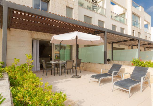 Liegestühle, Sonnenschirm und Tisch am Pool