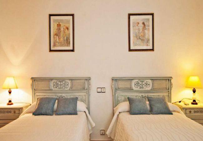 Zimmer mit zwei Betten und Nachttischen