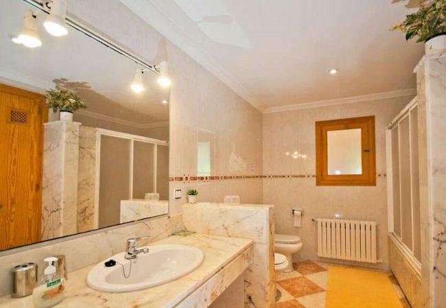 Badezimmer mit Badewanne und einem Waschbecken mit großem Spiegel