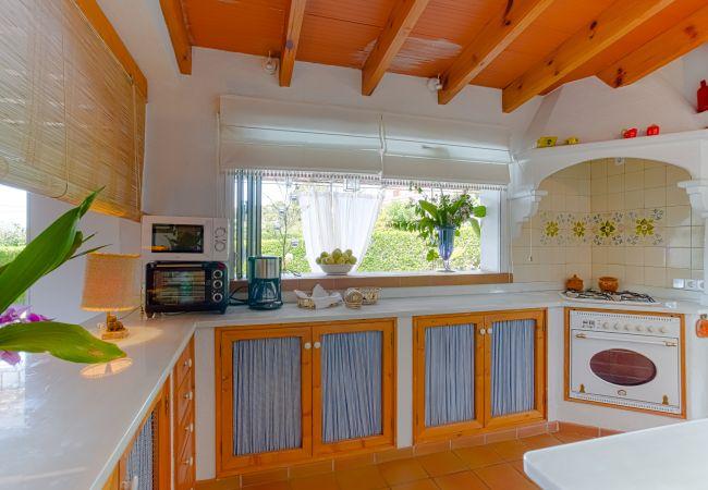 Rustikale Küche mit Blick auf den Pool