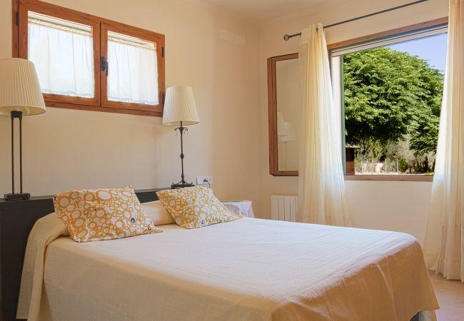 Schlafzimmer mit Doppelbett und Blick auf den Garten