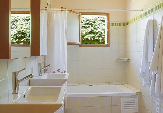 Badezimmer mit Doppelwaschbecken und Badewanne