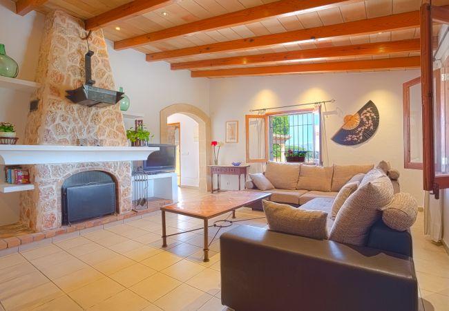 Wohnzimmer mit Sofa, Tisch und dekorativem Kamin