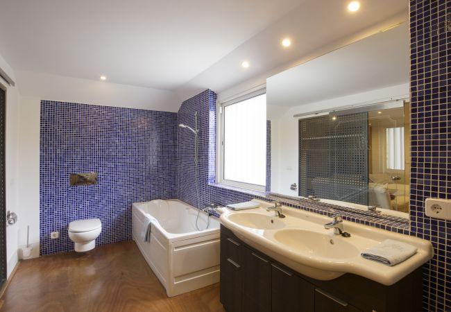 Badezimmer mit Badewanne und Doppelwaschbecken mit großem Spiegel