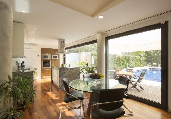 Voll ausgestattete Marmorküche mit Glastüren zum Pool