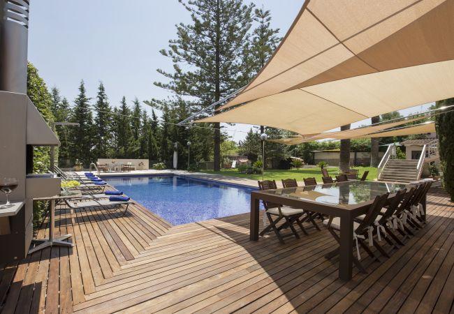Tisch für 8 unter Sonnenschirm und neben dem Pool