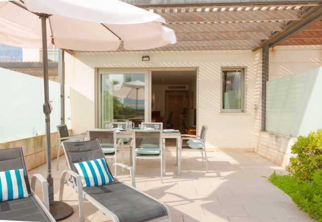 Terrace of the apartment with umbrella and access to the pool