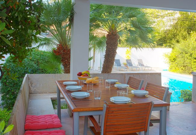 Covered terrace with table and pool view