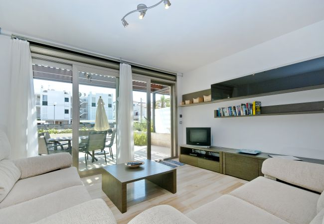 Living room with access to the covered terrace and the communal pool