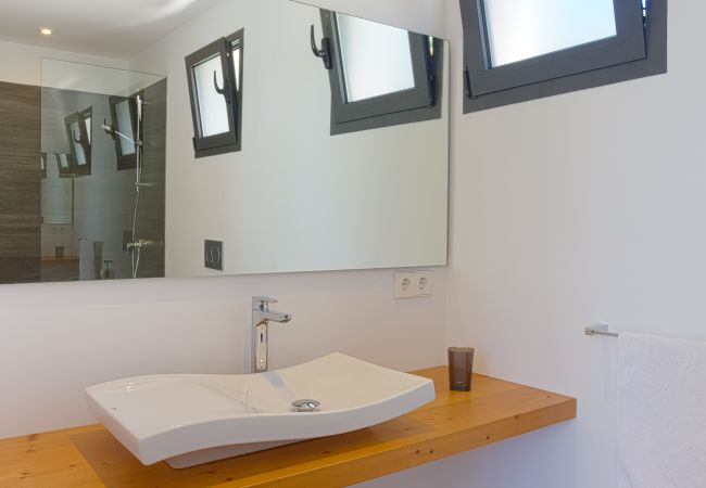 Washbasin and bathroom mirror en suite with shower.