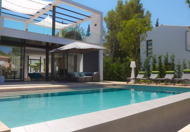Pool in front of the porch of the property with sun loungers and parasol