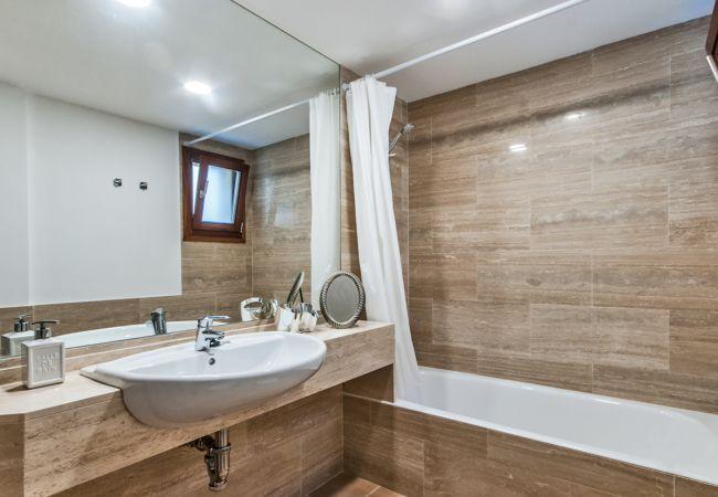 Bathroom with bathtub and large mirror