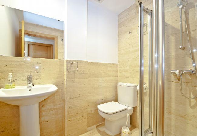 Baño con ducha y mampara de cristal con wc y lavabo