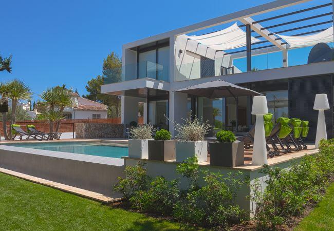 Fachada con terrazas y piscina privada con jardín