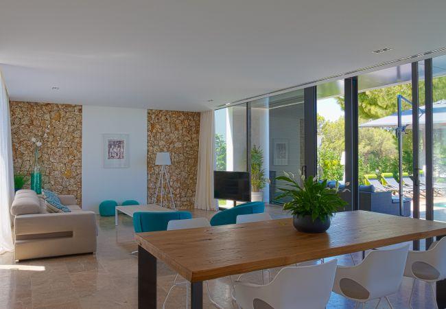 Salón comedor acristalado con vistas y acceso a la piscina