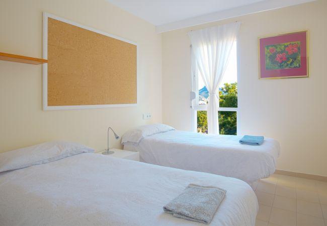 Camas individuales en dormitorio con gran ventana